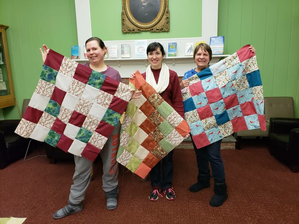 Three young ladies holding up quilts they have made