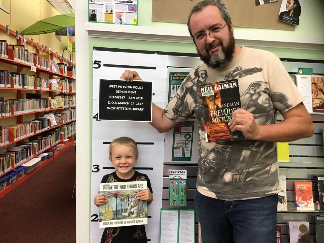 father and son holding up books for banned books week, including Where the Wild Things Are